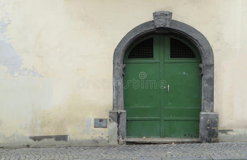 Porta verde velha do ferro em uma parede resistida gasto fotos de stock royalty free