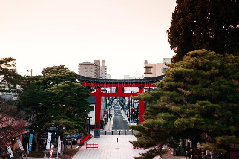Porta vermelha de Torii no santuário de Morioka Hachimangu em Iwate no por do sol com o céu morno do tom imagens de stock royalty free