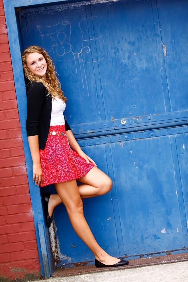 Porta vermelha do azul da saia do adolescente bonito fotos de stock