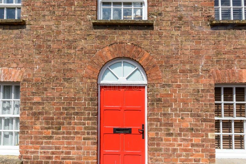 Porta vermelha na casa do tijolo vermelho imagens de stock royalty free