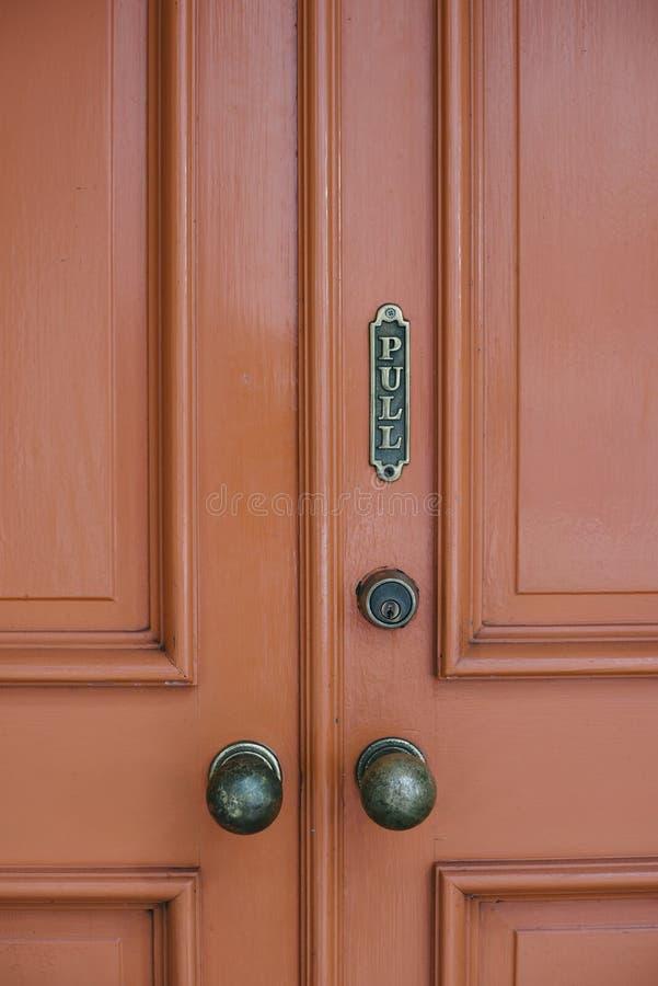 Porta vermelha velha com sinal da tração e botões de porta velhos foto de stock royalty free