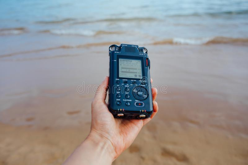 Portable audio recorder in hand recording ambient sounds of sea royalty free stock photography