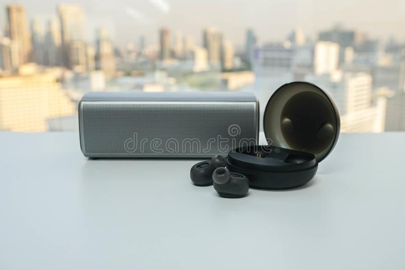 Portable bluetooth speaker and wireless earphone with trendy case for music stock photo