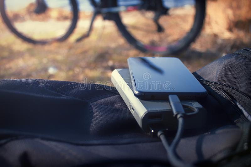 Portable charger charges the smartphone. Power Bank with cable against the background of bicycle.  stock photography