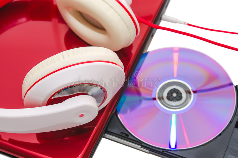 Portable computer with DVD disc and red white headphones royalty free stock photo