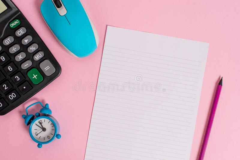 Portable electronic calculator wire mouse alarm clock wakeup pencil striped letter size sheet colored background Empty. Electronic calculator alarm clock mouse royalty free stock photography