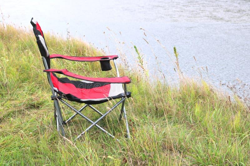 Portable folding turystyczny czerwony fotel na zielonej trawie latem fotografia stock