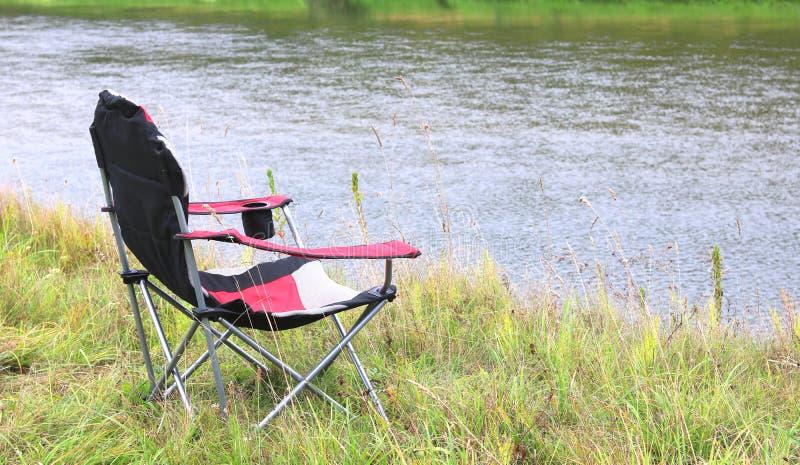 Portable folding turystyczny czerwony fotel na zielonej trawie latem zdjęcia stock