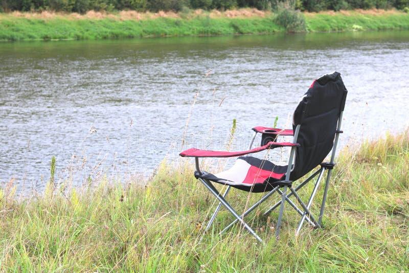 Portable folding turystyczny czerwony fotel na zielonej trawie latem obraz stock