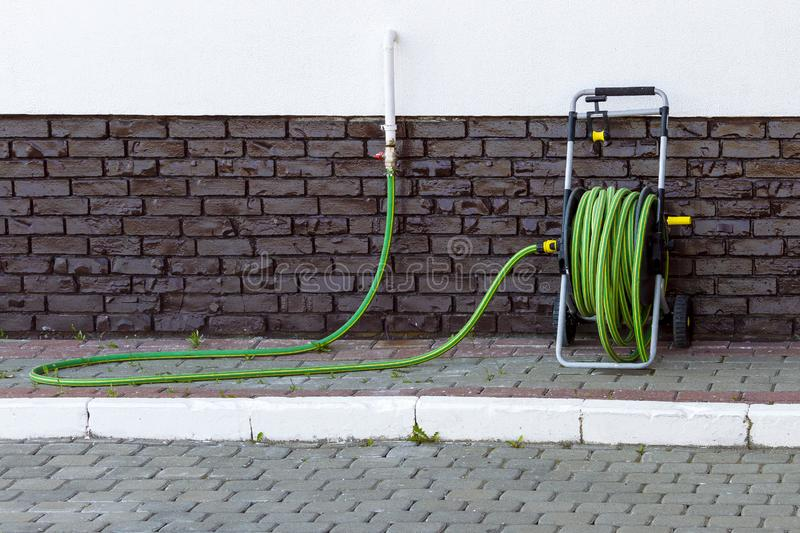 A portable green hose in a reel for watering lawn and flowers near the wall. The hose is connected to the water supply. View front stock images