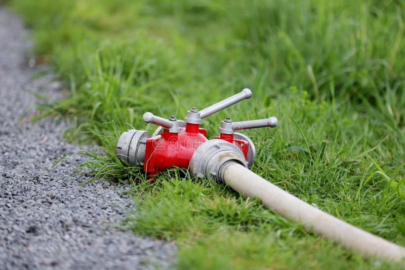 Portable hydrant with a hose. Water spout garden hose with valves on green grass on a summer day stock image
