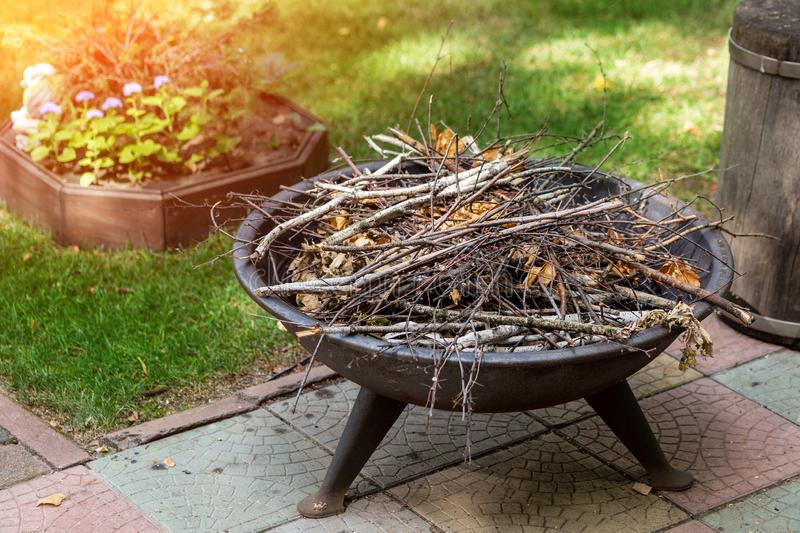 Portable iron fireplace with dry brushwood at backyard of summer cottage. Bonfire prepared for evening campfire stories stock photos
