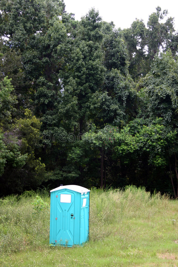 Portable john. Portable outhouse in a vacant lot royalty free stock photo