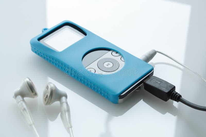 Portable media player. Portable mp4 media player with earphones on glass surface stock photo