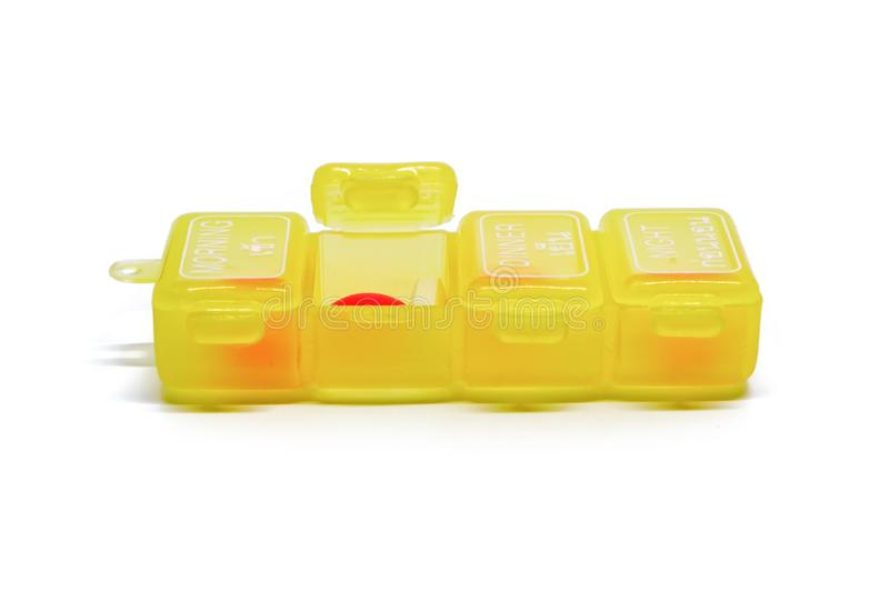 Portable medicine daily storage pill. With 4 separate compartments for morning, lunch, dinner and night on white background royalty free stock photography