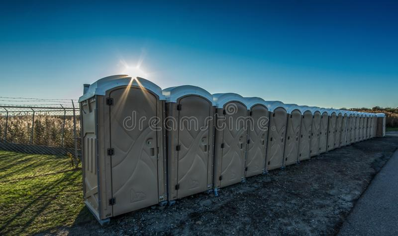 Portable Restrooms with Sunlight and Blue Sky. Row of portable restrooms with sun ray and blue sky and green grass stock images