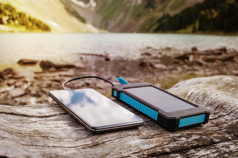 Portable solar panel for charging mobile devices stock images