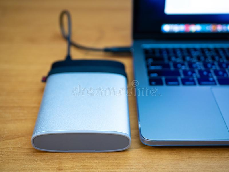 Portable ssd disk drive connected to laptop computer. Data information backup recovery concept stock photography