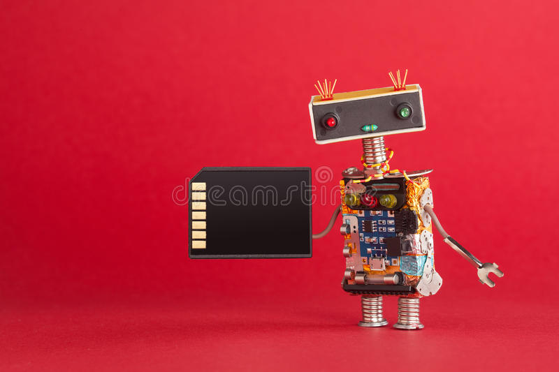Portable storage device memory card concept. Abstract robot system administrator with electronic computing chip circuit. On red background. Macro view copy royalty free stock photo