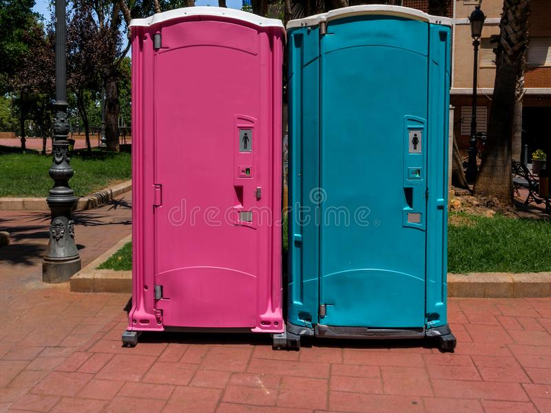 Portable toilets pink for men and blue for women royalty free stock images