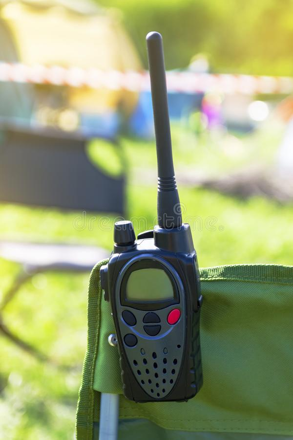 Portable walkie-talkie hanging on the back of a tourist chair. A portable walkie-talkie hangs on the back of a tourist chair. Summer, nature royalty free stock photo