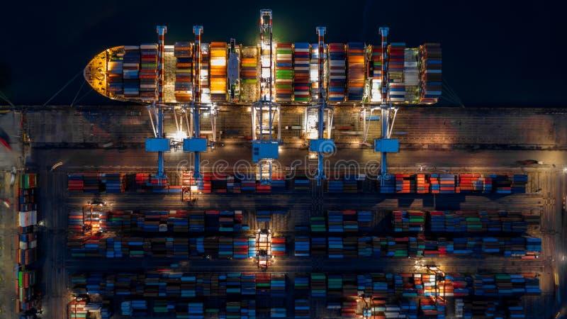 Portacontenedores en el negocio de las importaciones/exportaciones logístico en la noche, vista superior aérea portacontenedores imagen de archivo libre de regalías