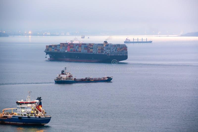 Portacontenedores grande anclada en la bahía del mar fotos de archivo