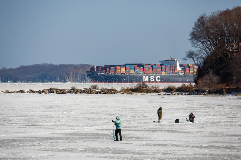 Portacontenedores grande está en la rada en una bahía congelada cerca del pueblo de Slavyanka en el Primorsky Krai fotos de archivo