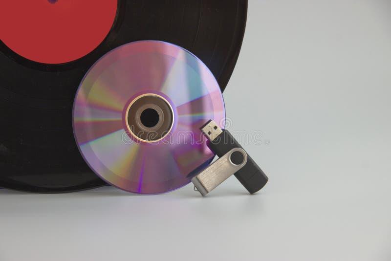Portadores de la información musical de diversos años, del vinilo, del disco laser y de memoria USB imagenes de archivo
