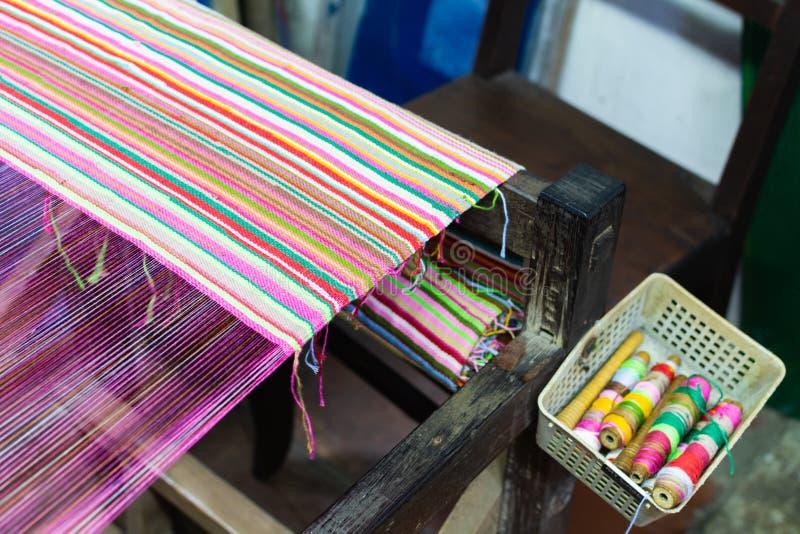 Portadores de relleno del telar con el paño tejido en fondo imagen de archivo libre de regalías