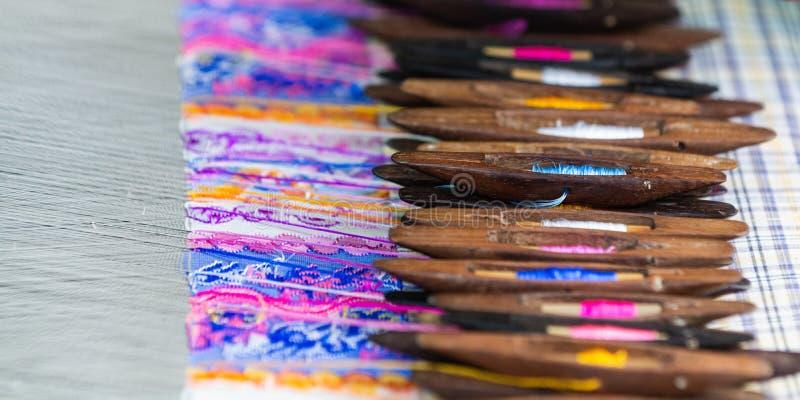 Portadores de relleno del telar con el paño tejido en fondo fotografía de archivo libre de regalías
