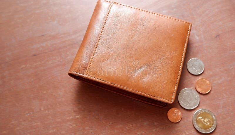 Portafoglio di Brown con le monete sul pavimento di legno fotografia stock libera da diritti