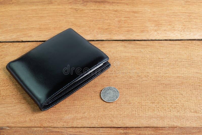 Portafoglio di cuoio nero con 5 monete di baht sul pavimento di legno immagini stock libere da diritti