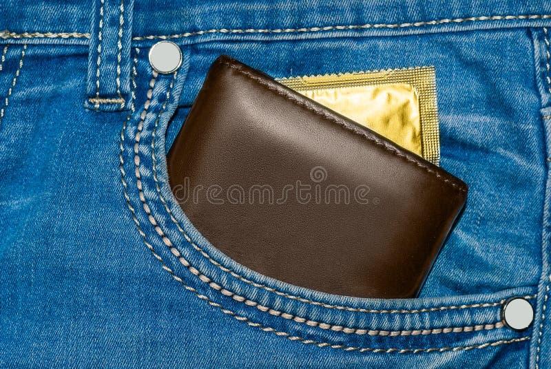 Portafoglio in una tasca delle blue jeans con un preservativo dell'oro immagine stock
