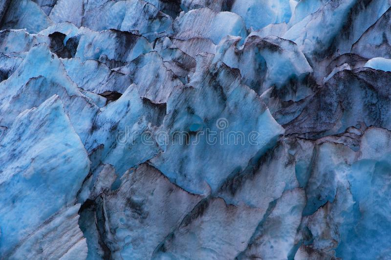 Shades of blue and patterns of black from a closeup view of the Portage Glacier in Alaska. stock images