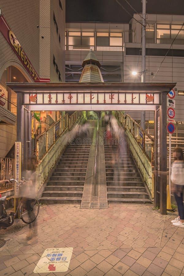 Portail lumineux en métal décoré des feuilles d'érable et un capital au fond des escaliers du pont de Momiji chez Nippori images stock