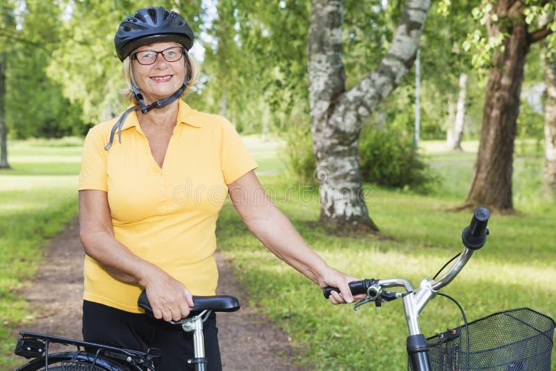 Portait av den härliga mogna kvinnan på parkerar med en cykel royaltyfria bilder