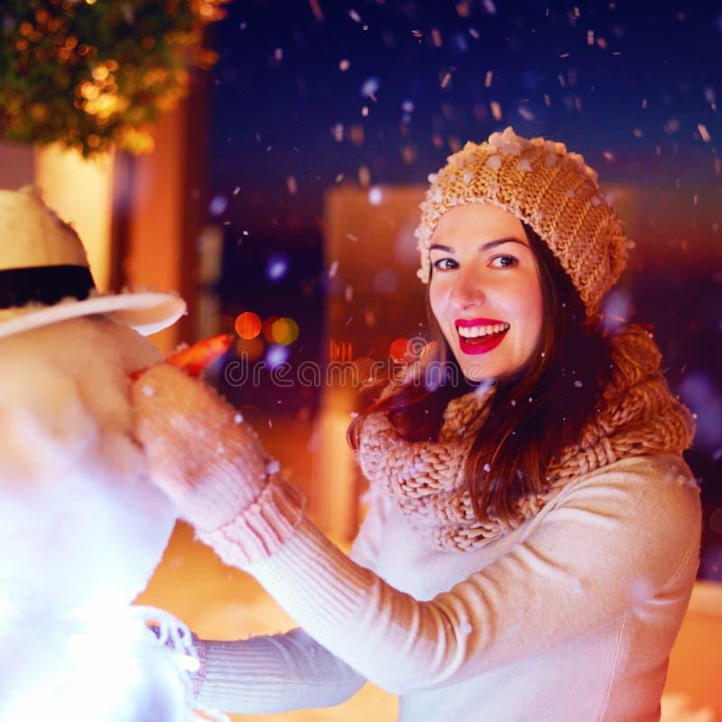Portait av den lyckliga kvinnadanandesnögubben under magisk vintersnö royaltyfria bilder