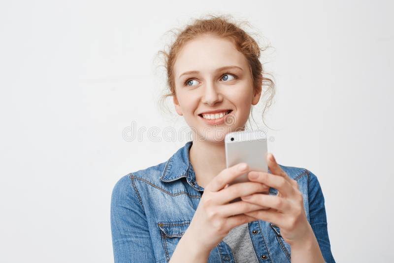 Portait av den tonårs- flickan för gullig mjuk rödhårig man med smutsigt hår som åt sidan ser och ler, medan rymma smartphonen oc royaltyfri fotografi