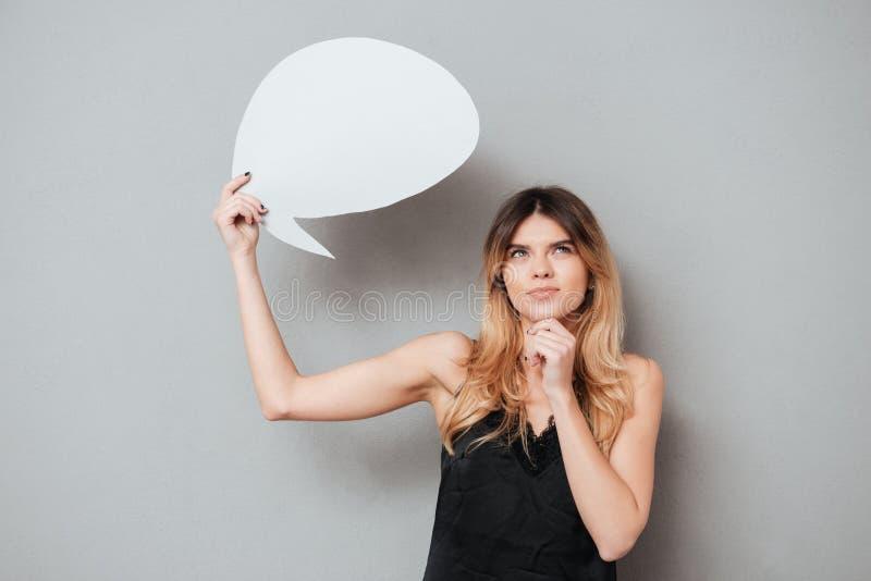 Portait av en hållande anförandebubbla för älskvärd eftertänksam flicka royaltyfri bild