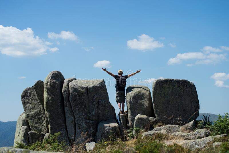 man with backpack openning arms on the megaliths at the top of the mountain royalty free stock photo