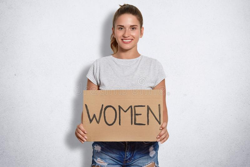 Portait of beautiful woman has gentle smile, dressed casually, holds plate with sign Women, being feminist, poses against white ba. Ckground, has dark hair royalty free stock photo