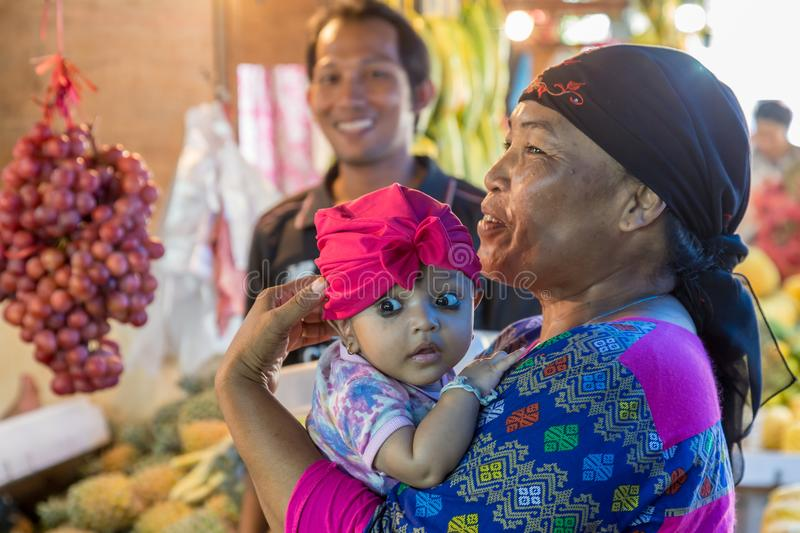 Portait of a colorful Indonesian baby. Surabaya, Indonesia - November, 05, 2017: Beautiful baby with her mother at the market in Surabaya in Indonesia stock images