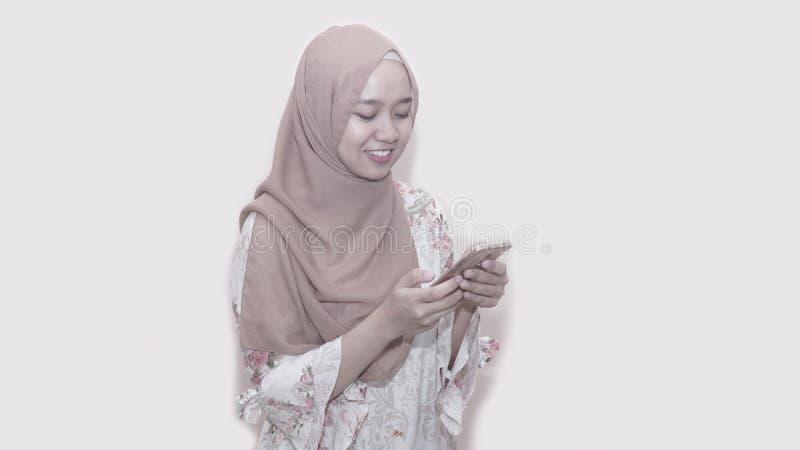 Portait d'?charpe principale de port ou de hijab de femme musulmane asiatique utilisant le smartphone photos libres de droits