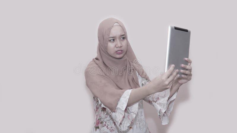 Portait de l'?charpe principale de port ou du hijab de femme musulmane asiatique jouant avec le PC de comprim? image libre de droits
