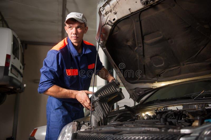 Portait del motor de coche de la fijación del mecánico en el taller de reparaciones foto de archivo libre de regalías