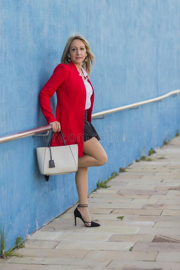 Portait di una donna elegante bionda che indossa appoggiarsi rosso del rivestimento fotografia stock libera da diritti