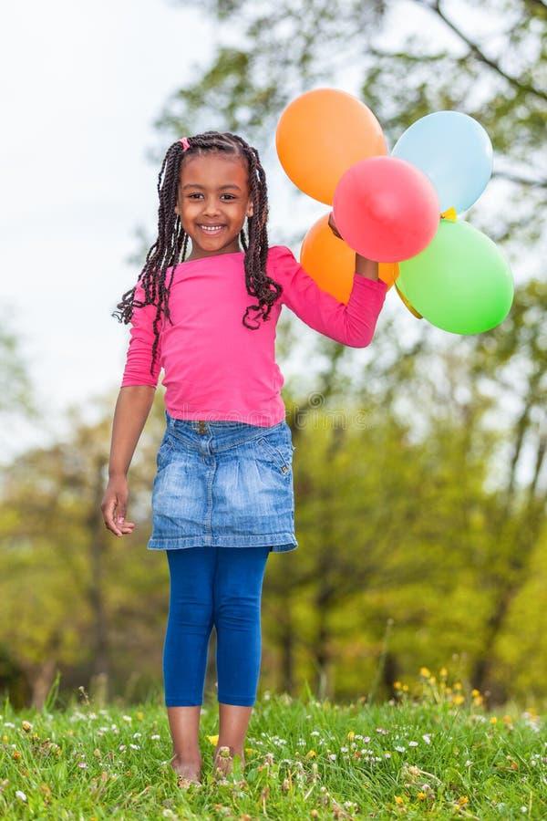 Portait extérieur d'une jeune petite fille noire mignonne jouant avec photos libres de droits