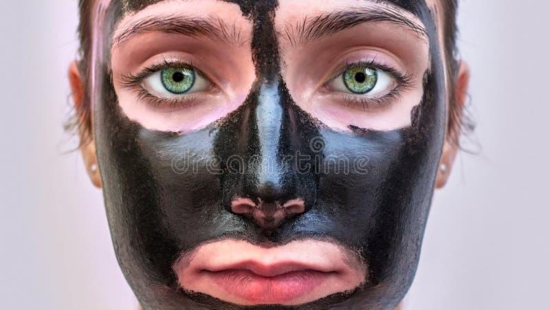 Portait kvinnas framsida med gröna ögon för svart hudbehandlingmaskering royaltyfri fotografi