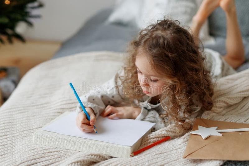 Portait of small lovely beautiful curly child draws pictures on blank white sheet of paper, wants to congratulate her stock images